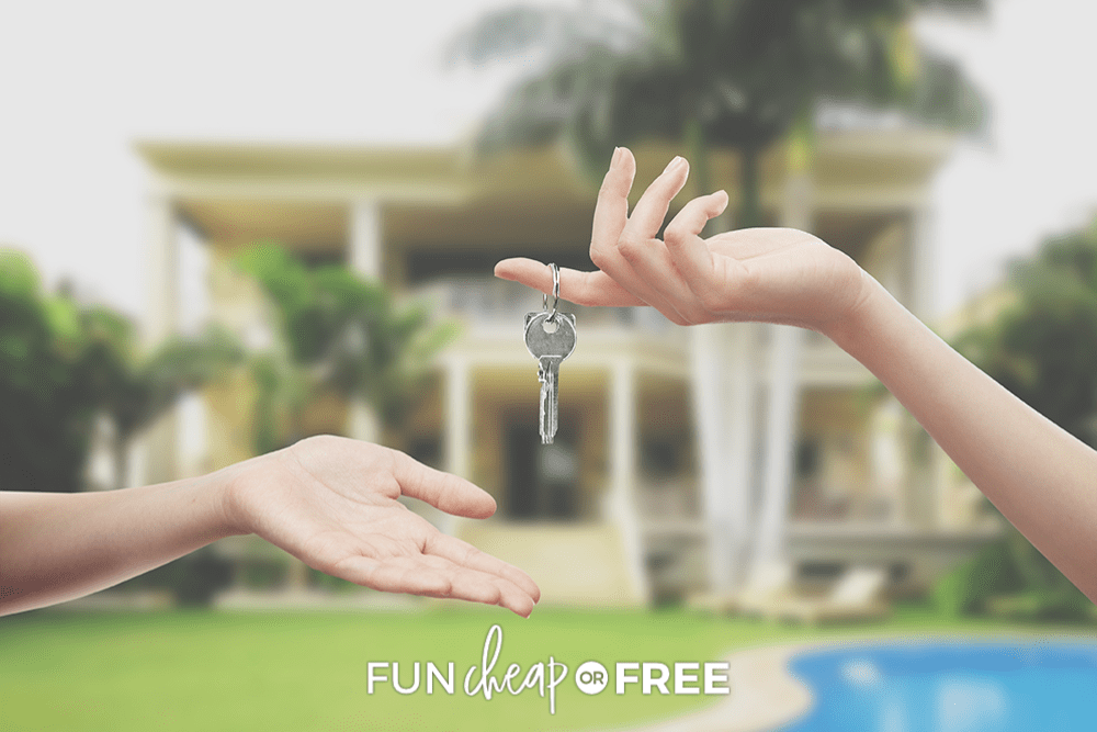 image of hand holding a key in front of a house, from Fun Cheap or Free