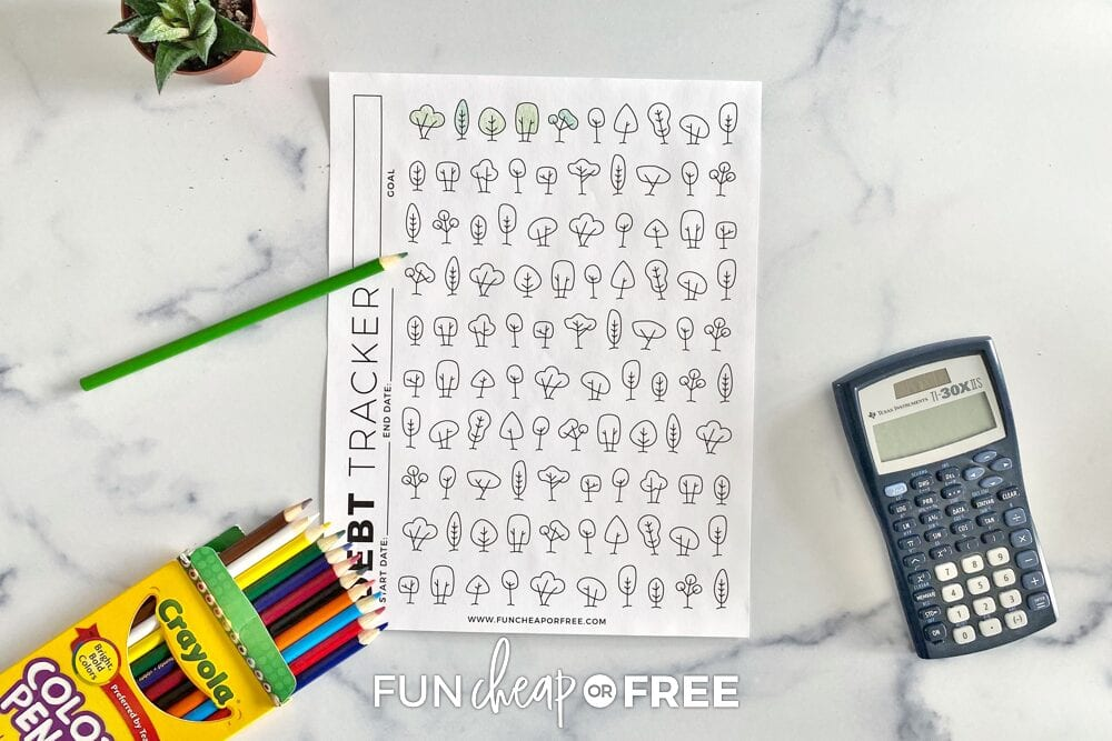 Printable debt tracker on a counter with colored pencils, from Fun Cheap or Free