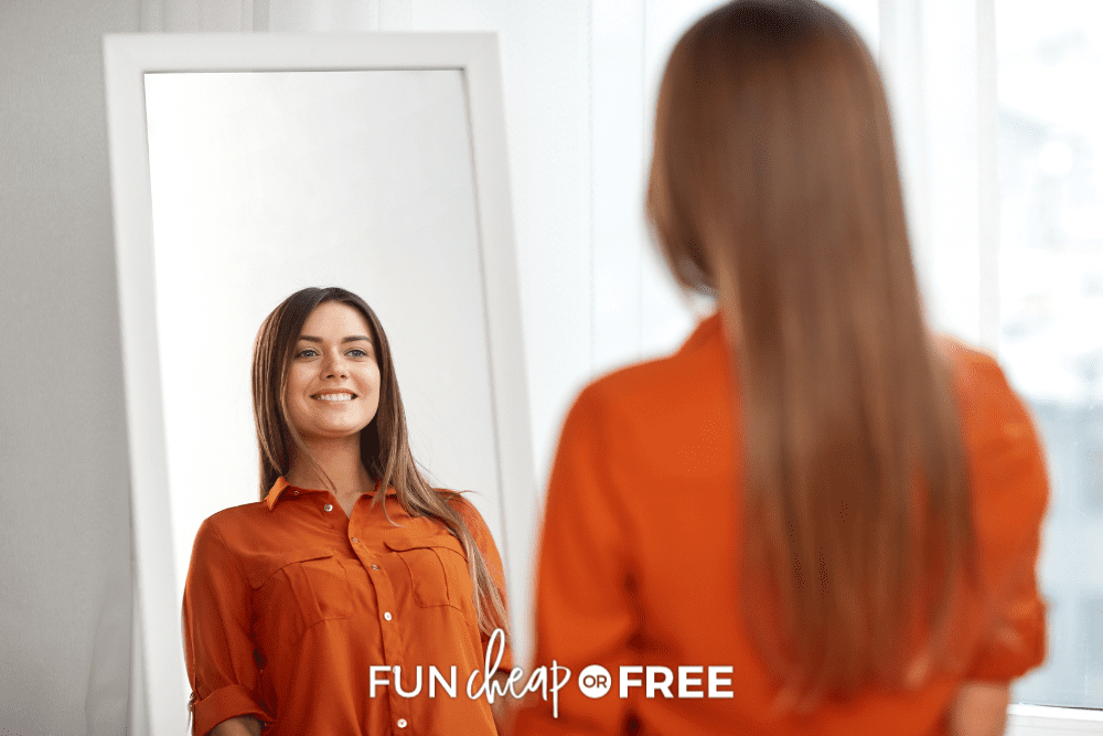 woman looking in mirror, smiling, from Fun Cheap or Free