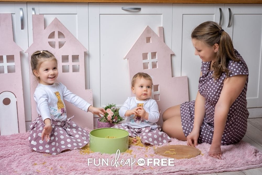 toddler girls and mom playing with dry pasta on floor, from Fun Cheap or Free