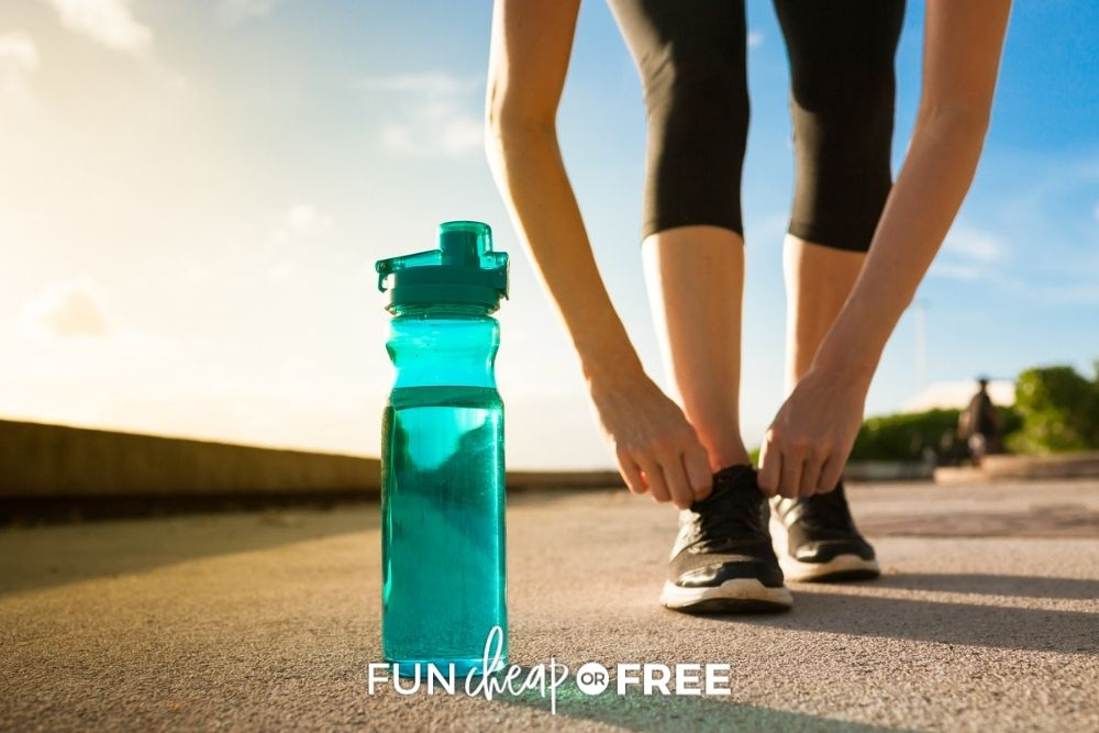 woman lacing up sneakers to run with water bottle, from Fun Cheap or Free