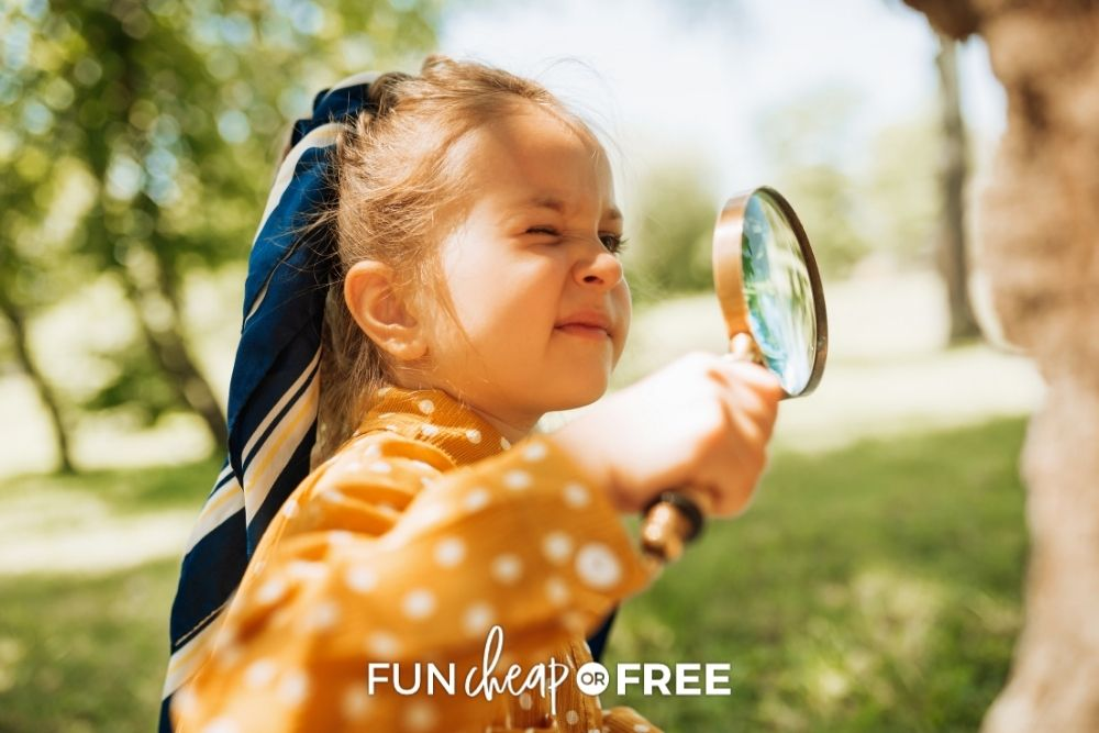 little girl playing outside with a magnifying glass, from Fun Cheap or Free