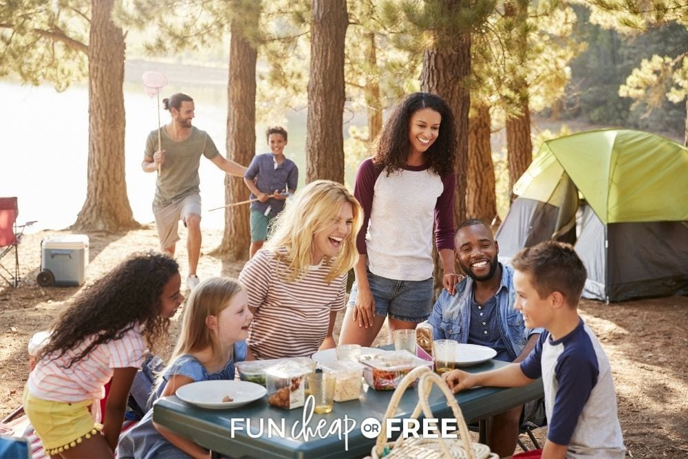 Family and friends gathered around picnic table at campsite from Fun Cheap or Free.