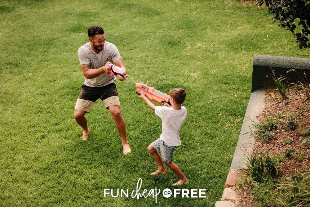 Father and son water gun fighting on camping trip from Fun Cheap or Free.