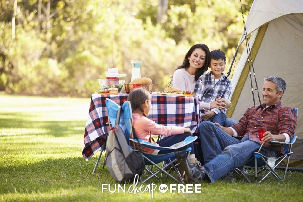 Family sitting around table at campsite by Fun Cheap or Free.