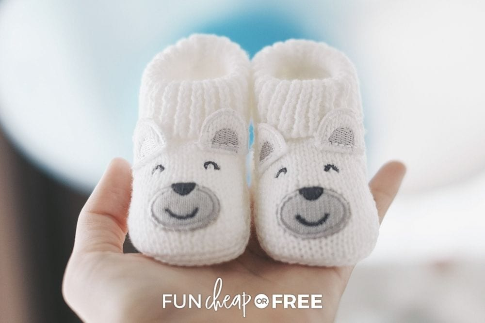 Hand holding baby shoes from Fun Cheap or Free.