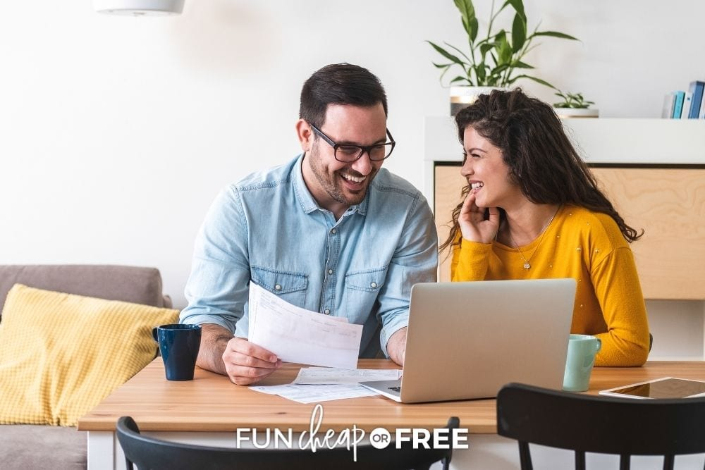 Couple smiling while paying bills from Fun Cheap or Free.