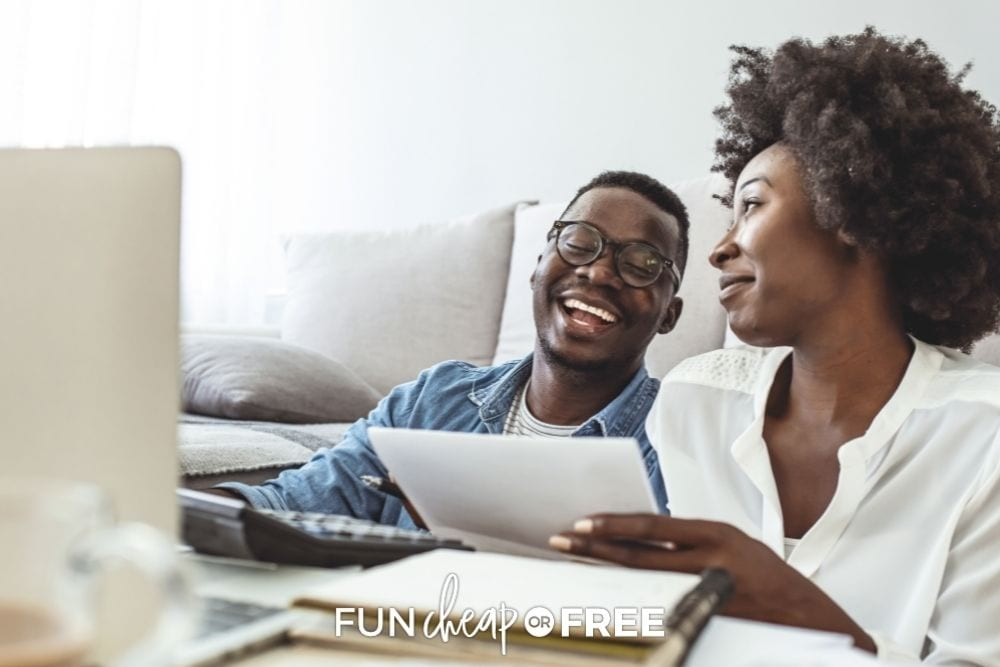 Couple laughing while paying bills from Fun Cheap or Free.