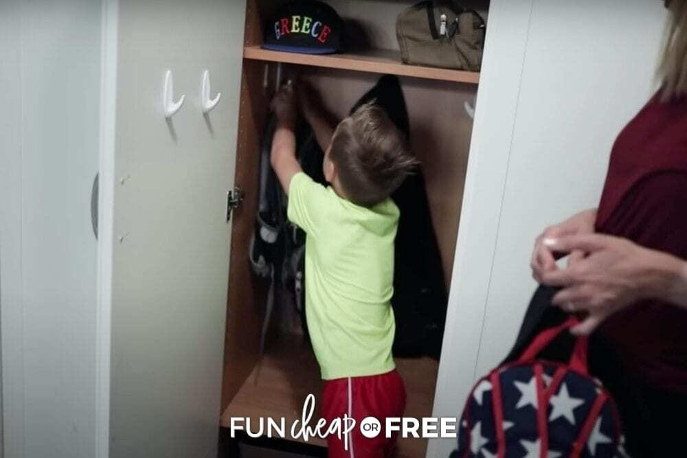Boy hanging something on a hook in a closet from Fun Cheap or Free.