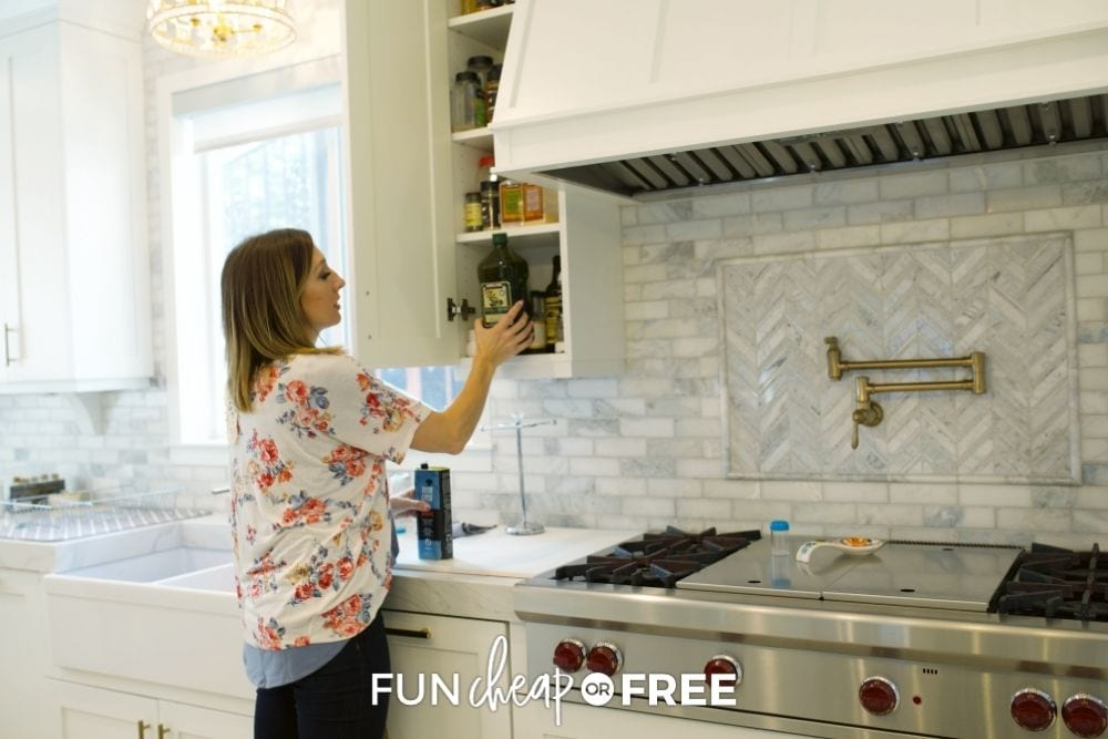 Jordan Page putting olive oil in a kitchen cabinet from Fun Cheap or Free.