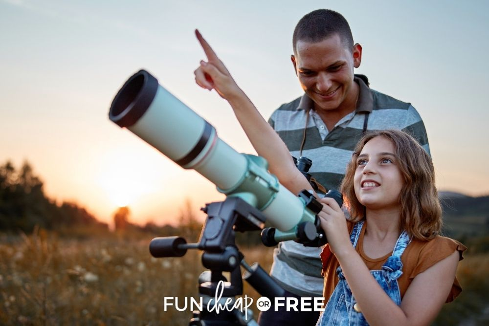 Dad and daughter stargazing through a telescope fromFun Cheap or Free.