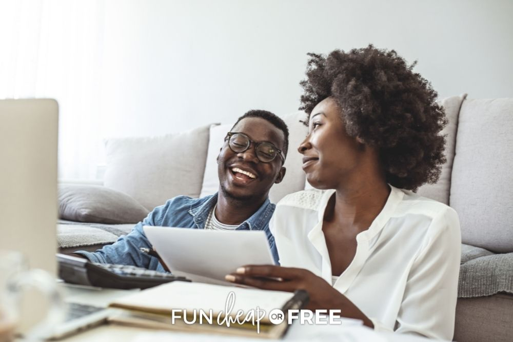couple with notebook discussing finances, from Fun Cheap or Free