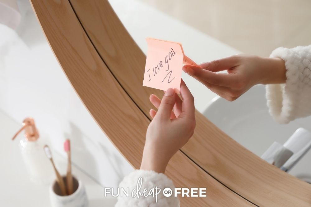 Hand putting post-it note on a mirror from Fun Cheap or Free.